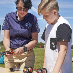 The workshop leader helps a boy build his K'Nex car