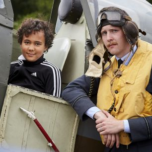 A boy sits in the spitfire, as the pilot re-enactor stands alongside