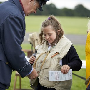 One of our pilot re-enactors helps a young pupil fasten a World War Two life jacket she's trying on