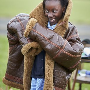 A young girl smiles as she tries on a very large, very think, pilot's flying jacket from World War Two
