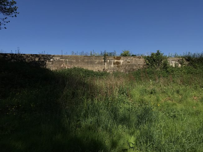 The shelter backed onto this concrete embankment opposite the rifle range wall. (May 2021) | Linda Duffield