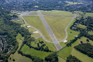 Modern aerial view of Kenley airfield, showing runway and surrounding trees and fields |  From Historic England