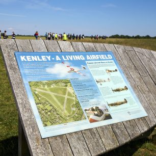 One of the signposts at Kenley, entitled 'A Living Airfield', with groups of children walking past in the background