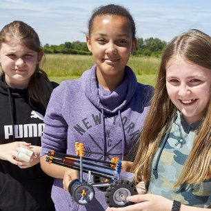 A group of girls pose proudly with their aerodynamic, blast powered, K'Nex car design