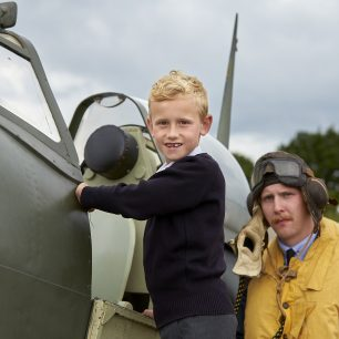 A young boy prepares to climb in and sit in the spitfire