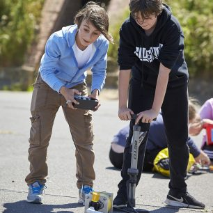 Two boys excitedly launch their K'Nex car using the foot pump, to take part in the competition