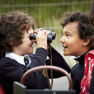 One boy pulls a face as another looks at him through a pair of old binoculars