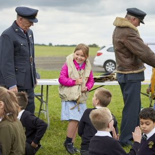 Two pilot re-enactors help two smiling girls try on World War Two life jackets