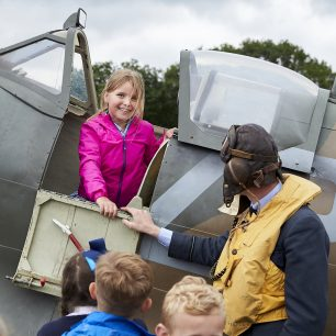 A boy smiles at the camera as she sits inside the spitfire, aided by one of the re-enactors
