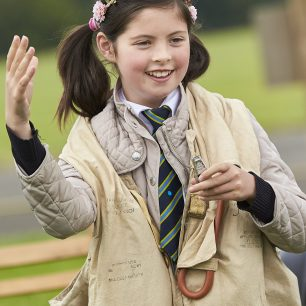 A girl waves to her classmates as she tries on an old World War Two life jacket