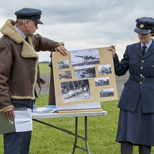 A pilot and a WAAF re-enactor hold up a display of photographs depicting the Battle of Britain
