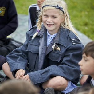 A girl sits listening to the workshop, wearing a Group Commander's jacket