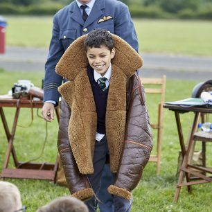 A boy grins at his class as he wears the huge pilot flying jacket