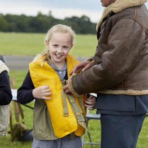 A girl smiles at the camera as she tries on a yellow rubber life jacket