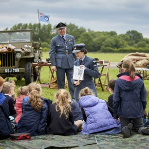 A WAAF re-enactor sits in front of a group of children, giving them a lesson, as they sit and listen