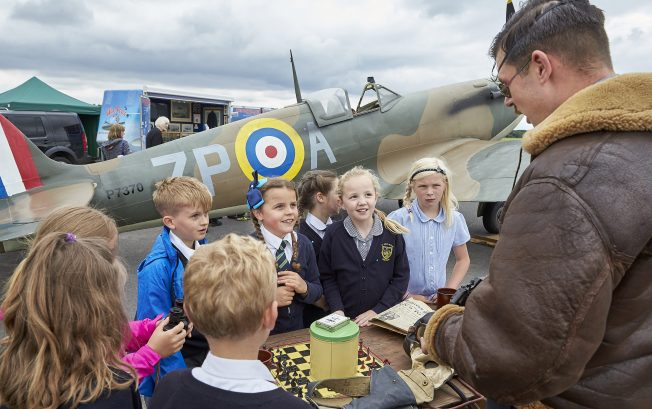 Children handle artefacts, including an old chess set, and chat with one of the re-enactors