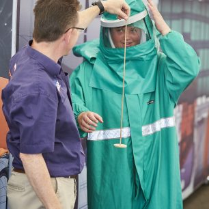 A boy tries on a big green overall, taking part in a demonstration, to show what the driver would wear