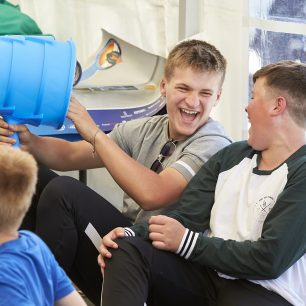 Two boys laugh as one plays with a piece of equipment