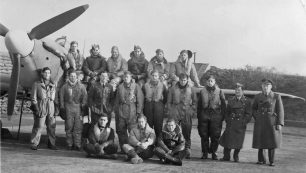 Photo shows 18 soldiers next to an airplane wing