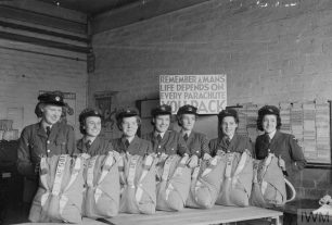 Seven members of the WAAF, each with over two and a half years service at the Parachute Training School at Ringway, 3 May 1944. The women have, between them, packed nearly fifty thousand parachutes to date.