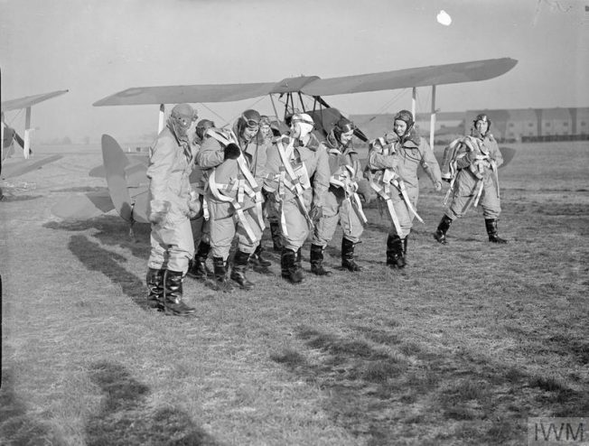 The first pilots of the ATA Womens' Section pilots walking past newly-completed De Havilland Tiger Moths awaiting delivery to their units at Hatfield, Hertfordshire. They are, (right to left): Miss Pauline Gower, Commandant of the Women's Section, Miss M Cunnison (partly obscured), Mrs Winifred Crossley, The Hon. Mrs Fairweather, Miss Mona Friedlander, Miss Joan Hughes, Mrs G Paterson and Miss Rosemary Rees. | © IWM (C 382)