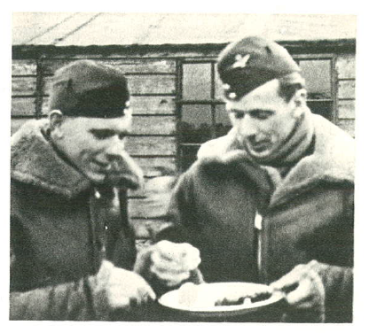 Commanders of unit A and B of Squadron 302, Captains Tadeusz Czerwiński and Julian Kowalski sharing a traditional Easter egg, Kenley Airport 1941.