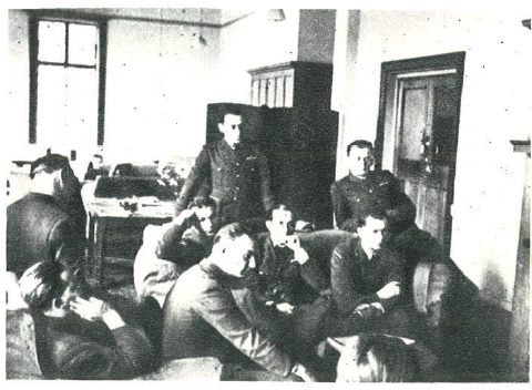Officers' mess at RAF Kenley, Easter 1941. Pilots of Squadron 302 focused listen to the Commander Major Piotr Łaguna. From the right: Officers Stanisław Chałupa, Marceli Neyder, Zbigniew Wróblewski, from side Jan Maliński, deep inside Władysław Gnyś, Ryszard Narucki, in armchair Stanisław Łapka, from side, always avoiding photos, doctor of the Squadron, Dr. Stanisław Pokrzywnicki.