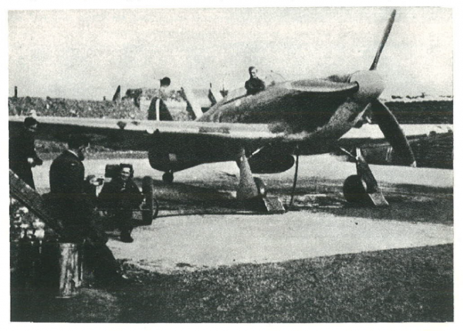 Despite such protected location, Squadron 302 lost several Hurricanes as a result of bombing. On the left wing a parachute prepared for the pilot. Engine battery on a trolley attached to the engine. A fire extinguisher by the wall. Three maintenance technicians and sergeant Joseph Gumowski supervising everything. Further away an emergency alarm speaker. RAF Kenley.