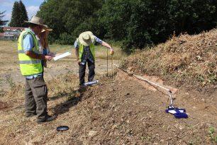 Volunteers measuring height of brick wall on wing