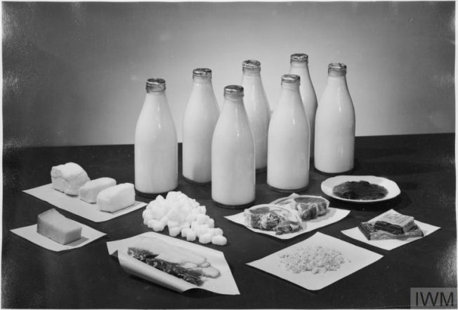 THE WEEKLY RATION FOR TWO PEOPLE, UK, 1943 (D 14667) This photograph shows the amounts of milk, sugar, bacon, cheese, butter and chocolate received by two people per week in Britain.