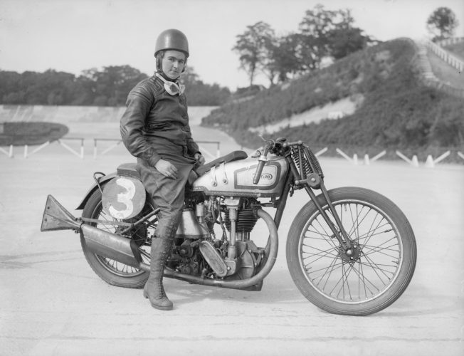 July 1935: Miss Beatrice Shilling sits astride her Norton motorcycle at the Brooklands race track.