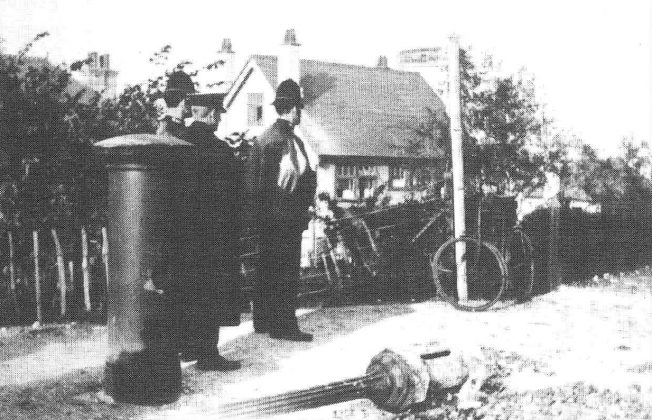 The aftermath of the bomb which hit the hard chalk road at Hall Way / Downscourt Rd fracturing a gas main, uprooting a lamp-post and holing a pillar box.  | Bourne Society