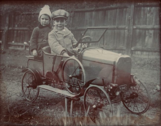 Hugh Henry-May (left) and his brother Roy Athow Henry-May in their pedal car. | Michael Henry-May