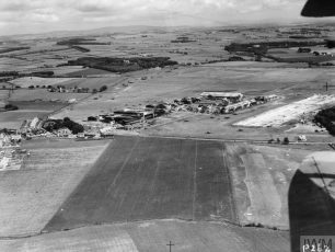 ROYAL AIR FORCE FLYING TRAINING COMMAND, 1940-1945. (HU 60596A) Oblique aerial view of Prestwick airfield from the west, showing the northern section of the airfield, including the Scottish Aviation Ltd complex, and the threshhold of the 6,600 ft x 300 ft concrete main runway (14/32) under construction (extreme right). Immediately to the left of the runway can be seen the remains of the Scottish Flying Training School buildings. | IWM Online Collection (IWM HU 60596A)